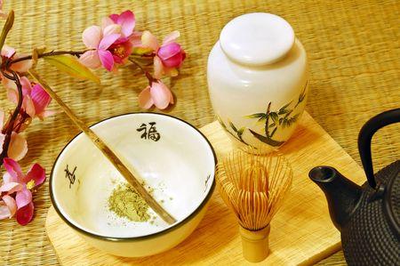 Tools für die japanische Tee-Zeremonie (chado). Ein Pinsel aus Bambus und eine Teetasse mit grünem Tee genannt Matcha auf hölzernen Fach.