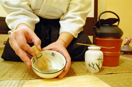 matcha: Tools used for Japanese tea ceremony (chado). A brush made of bamboo and a teacup with green tea called matcha on wooden tray. And tea master in kimono.