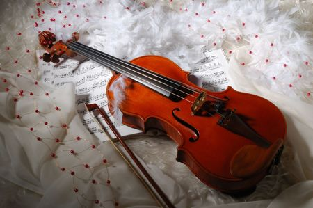 Violin and notes on silk background with boa and furs photo