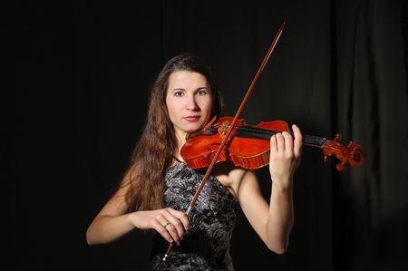 Beautiful violinist musician playing on black photo