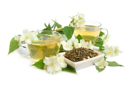 Organic jasmine tea leaves with fresh jasmine flowers and cups of tea on white background photo