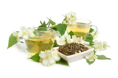 Organic jasmine tea leaves with fresh jasmine flowers and cups of tea on white background photo