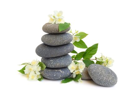 Stack of black stones for hot stones spa treatment and jasmine flowers on white background photo