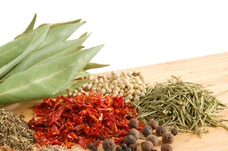 karri: Piles of spices on wooden background. Fresh bay leaves, whole black and white pepper, coriander, rosemary, caraway-seeds, dry paprika.