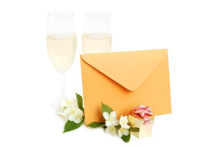 Champagne flutes, jasmine flowers, envelope and box with gift on white background photo