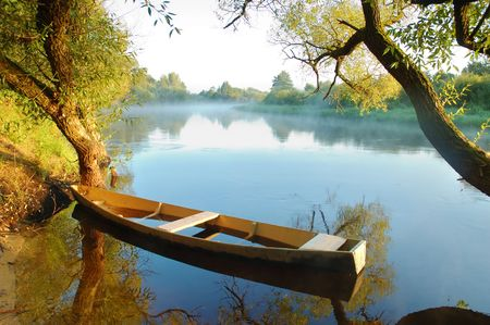 Beautiful autumn river and yellow rowing boat on a tranquil early morning Stock Photo