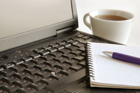 Spiral Notebook, pen and cup of coffee on laptop keyboard Stock Photo