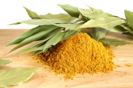 Piles of spices and fresh bay leaves on wooden background