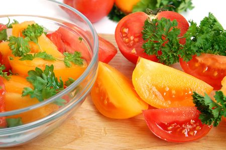 Fresh salad in glass bowl with greens and tomatoes on white background photo