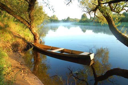 Beautiful autumn river and yellow rowing boat on a tranquil early morning Stock Photo - 5731202