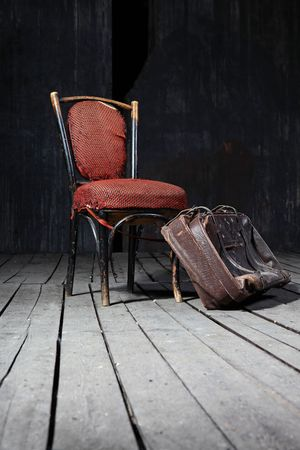 Old fashioned chair and well-traveled vintage suitcase on wooden floor Stock Photo - 5731316