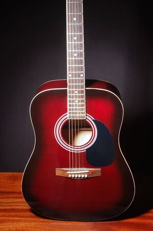 Detail of a red guitar on dark background photo