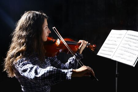 Beautiful violinist musician with sheet music on a stand on black background photo