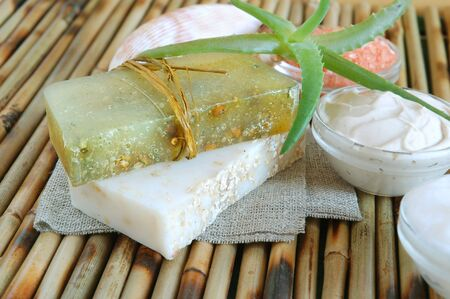 Handmade oatmeal soaps, facial mask, salt and hand cream on green on bamboo mat