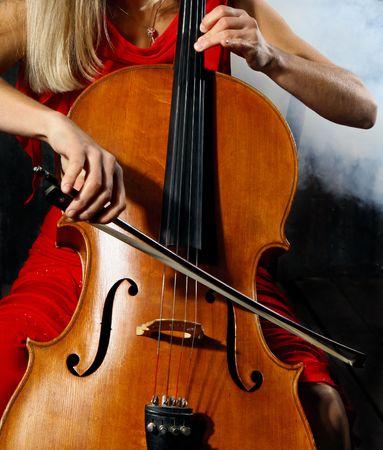violines: Close up de un m�sico violonchelo sobre fondo oscuro