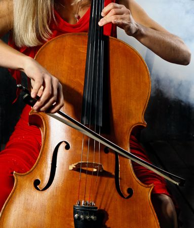 violins: Close up of a cello musician on dark background