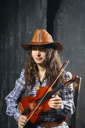 Beautiful violinist country performer on grey wall background photo