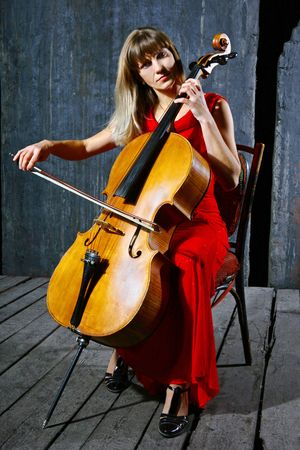 Beautiful cello musician on grey wall background photo