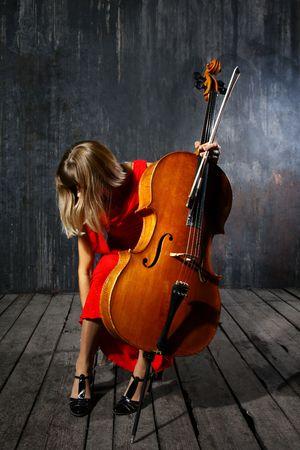 cello: Bella musicista violoncello su sfondo grigio muro