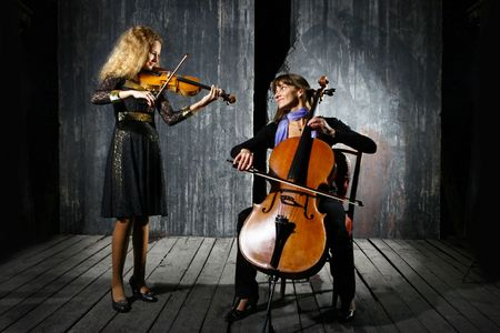 violas: Daughter and mother playing on cello and violin on grey wall background Stock Photo