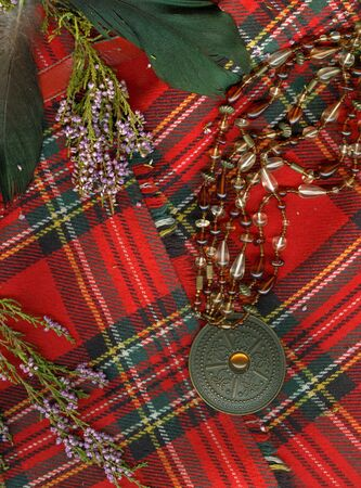Red scottish plaid with plume, heather and old medallion. photo