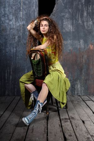 Attractive young woman sitting on a chair on wooden floor in a studio photo