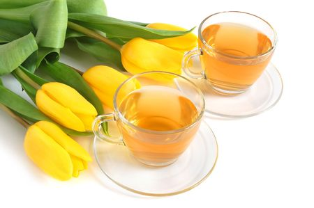 Class cups with green tea and colored tulips on white background photo