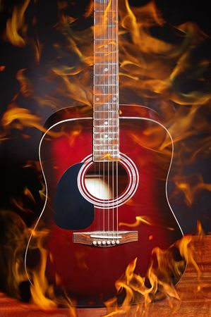 Acoustic classical guitar in flame on black photo