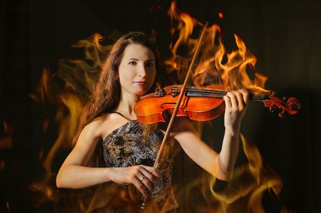 Beautiful violinist in flame playing on black photo