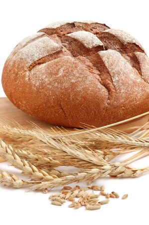 Homemade whole bread and stalks of wheat on a white background photo