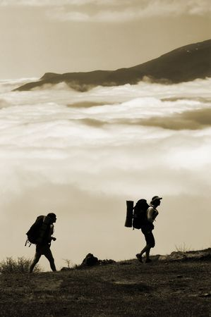 Two hikers with backpacks climbing a peak on cloud sky background photo