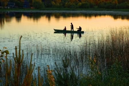 canoa: Silueta de tres pescadores en un pequeño bote a orillas de un lago al atardecer