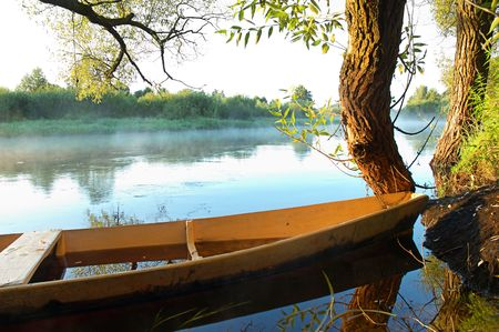 rowing boat: Beautiful autumn river and yellow rowing boat on a tranquil early morning Stock Photo