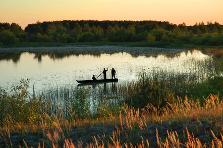 Silhouette of three fishermen in a small boat on a lake at sunset photo