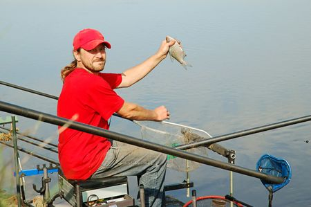 Fisherman holding a bream fish on beautiful river background Stock Photo - 7440780