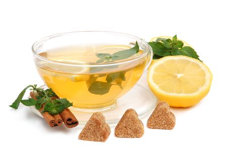 Cup of green tea with mint leaves, lemon, heart-shaped cane sugar and cinnamon sticks on white background photo