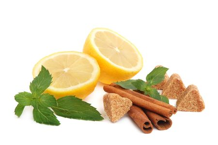 Lemon citrus with mint leaves, heart-shaped cane sugar and cinnamon sticks on white background photo