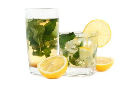 Glasses of iced tea with lemon mint leaves and ice on white background photo