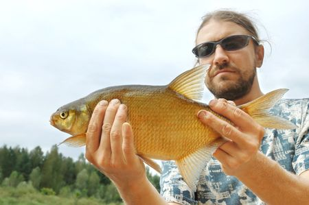 Fisherman holding a rudd fish on the shoreline of a river photo