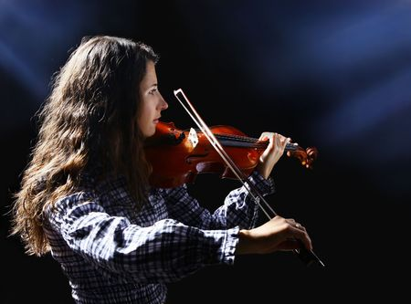 Beautiful violinist musician on black background