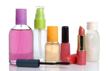 Perfume in bottle cream, nail, mascara and lipstick over white background photo