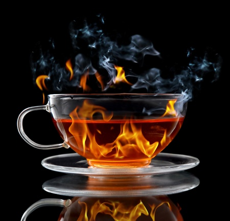 boiling water: Class cup with burning hot tea on black background Stock Photo