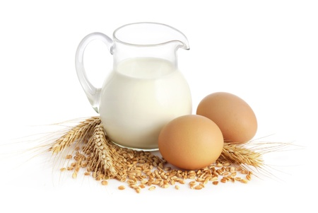 bakery products: Glass jug with milk, wheat seeds and two eggs on white background