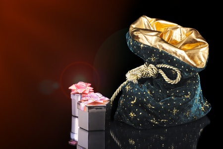 Christmas sack with golden boxes on black background photo