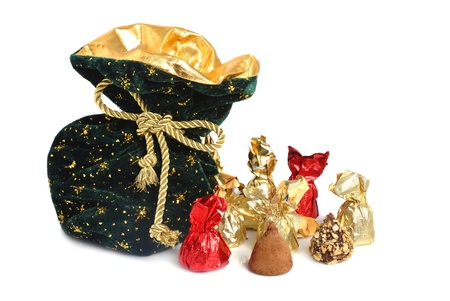 Christmas sack with golden ribbon full of chocolate candies on white background photo