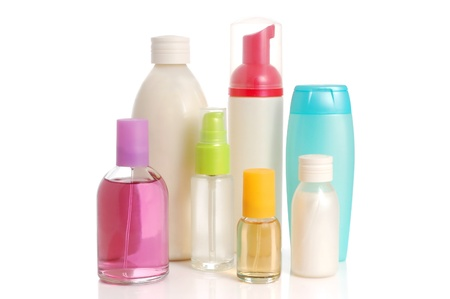 Blank bottles of shampoo, conditioner, perfume and pink salt over white background