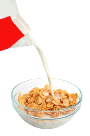 Bowl of cornflakes with pouring milk on white background photo