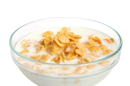 Bowl of cornflakes with milk on white background photo