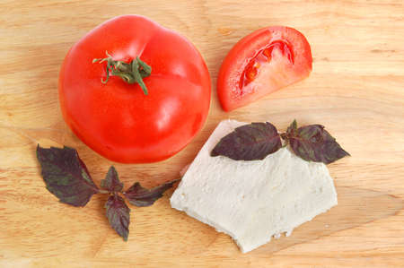 Tomatoe with white cheese slices and basil on cutting board background photo