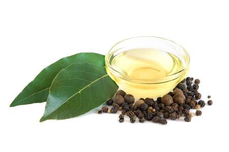 Fresh bay leaves, vegetable oil and black peppercorns on white background photo